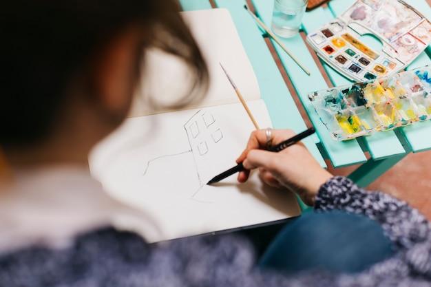 Femme sans visage, dessiner des bâtiments