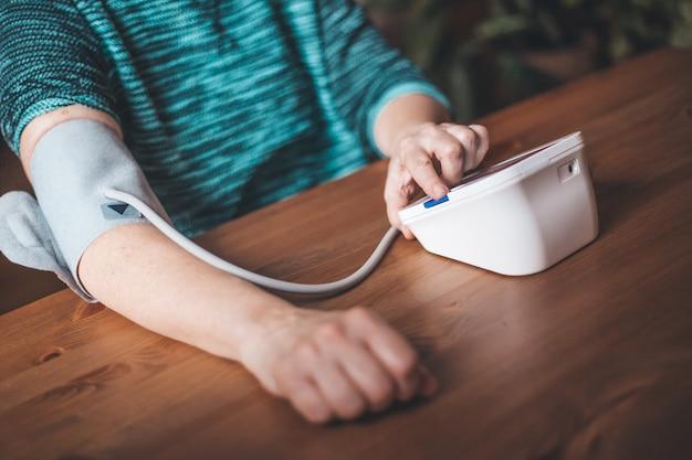 Femme santé vérifier la pression artérielle et la fréquence cardiaque à la maison avec la pression numérique, la santé et le concept médical