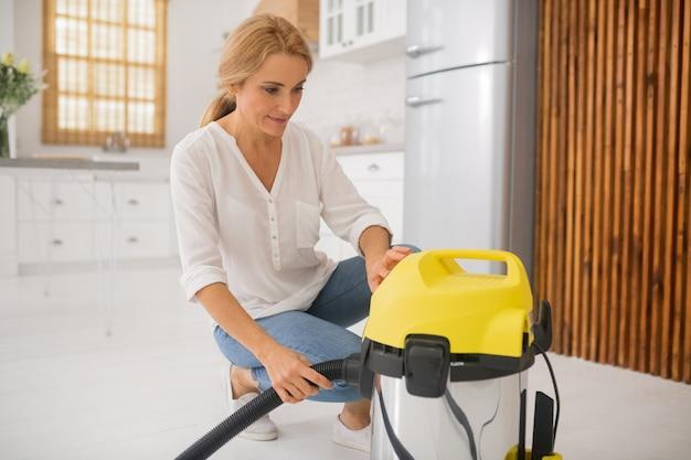 Femme satisfaite près de l'aspirateur jaune à la maison dans une cuisine lumineuse de bonne humeur