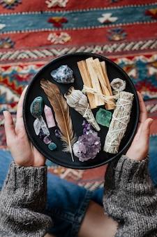 Femme avec de la sauge et des cristaux prêts pour le maculage