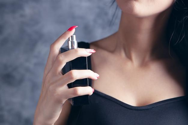 La femme saupoudre le parfum sur son cou