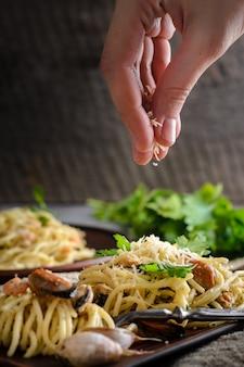 Une femme saupoudre une pâte de crevettes et de moules au parmesan dans une sauce crémeuse.