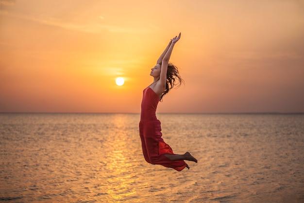 Femme sautant belle silhouette contre la mer et l'aube. tourisme, voyage, mouvement, joie, coucher de soleil