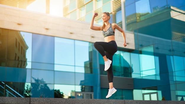 Femme sautant et courant contre la surface de la ville urbaine