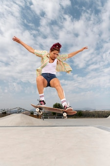Femme sautant avec skateboard full shot