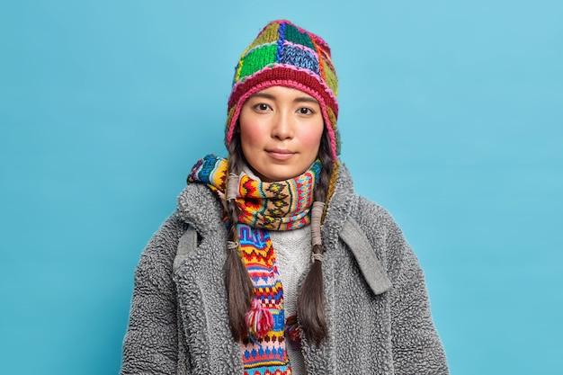 Femme scandinave sérieuse avec des nattes regarde calmement à l'avant vêtue de vêtements d'hiver chauds pose sur mur bleu