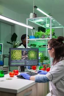 Femme scientifique chimiste tapant l'expertise en biochimie sur ordinateur