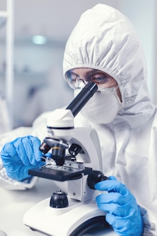 Femme scientifique en combinaison faisant une enquête sur les coronavirus en regardant au microscope. chercheur chimiste pendant une pandémie mondiale avec un échantillon de contrôle de covid-19 dans un laboratoire de biochimie