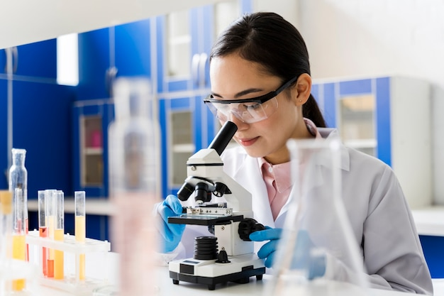 Femme scientifique dans le laboratoire en regardant à travers le microscope