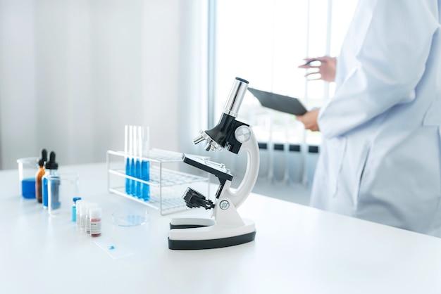 Femme scientifique debout pour lire le résultat du vaccin contre le coronavirus sur le rapport après avoir utilisé un microscope et un tube à essai avec un liquide bleu pour expérimenter produire le vaccin covid-19 en laboratoire