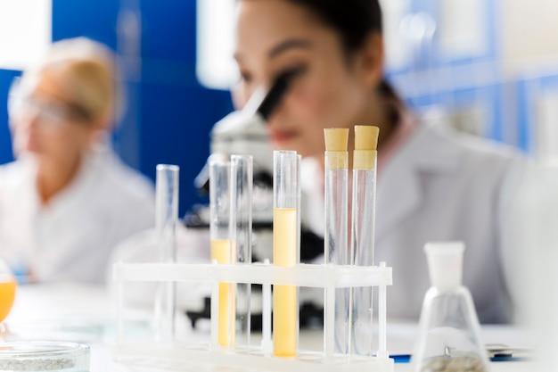 Femme scientifique défocalisée dans le laboratoire à l'aide d'un microscope