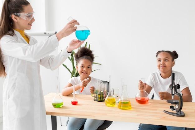 Femme scientifique enseignant la chimie des filles tout en tenant la potion
