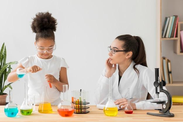 Femme scientifique enseignant des expériences scientifiques fille