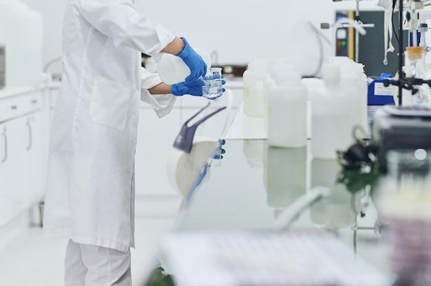 Femme scientifique mains avec des gants de protection travaillant en laboratoire