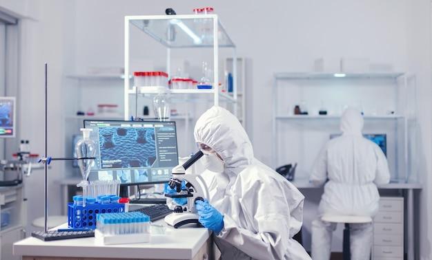 Femme scientifique médicale assise sur le lieu de travail en laboratoire regardant au microscope. chercheur chimiste pendant une pandémie mondiale avec un échantillon de contrôle de covid-19 dans un laboratoire de biochimie