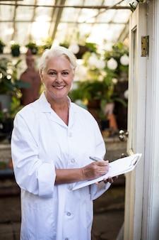 Femme scientifique avec presse-papiers à la porte