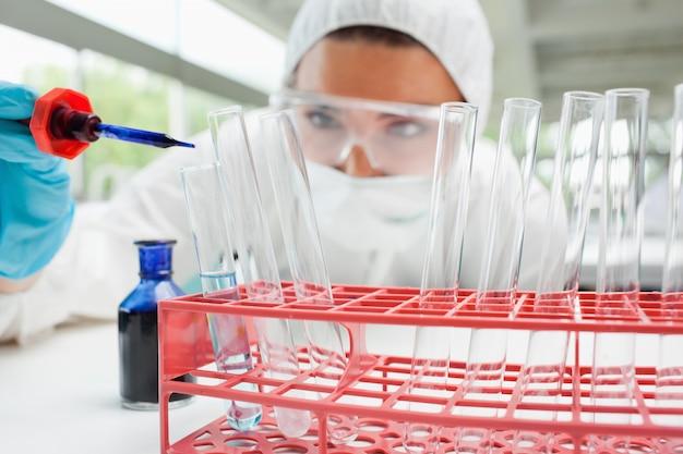 Femme scientifique protégée laissant tomber un liquide bleu dans un tube à essai