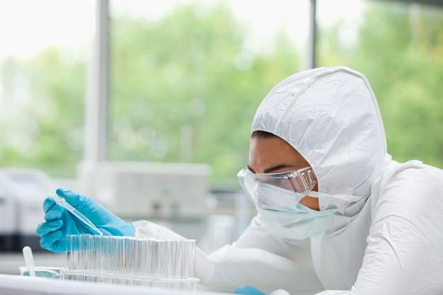 Femme scientifique protégée laissant tomber le liquide dans un tube à essai