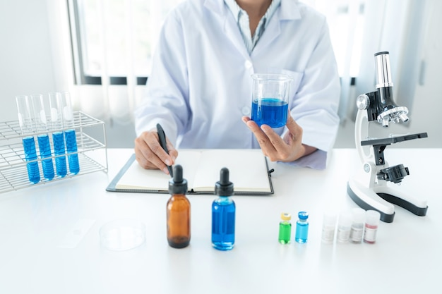 Femme scientifique tenant un bécher dans ses mains et écrivant un rapport de résultats sur un ordinateur portable tout en travaillant à l'analyse et au développement d'un vaccin contre le coronavirus en laboratoire
