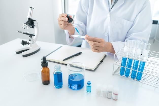 Femme scientifique tenant un compte-gouttes pour déposer un échantillon de solution sur la plaque de verre pour microscope et liquide bleu dans un tube à essai tout en travaillant à l'analyse et au développement d'un vaccin contre le coronavirus en laboratoire