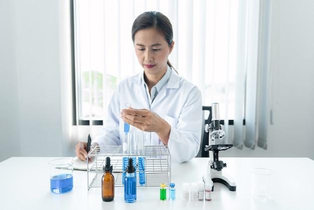 Femme scientifique tenant un tube à essai dans ses mains et écrivant le rapport de résultat sur un ordinateur portable