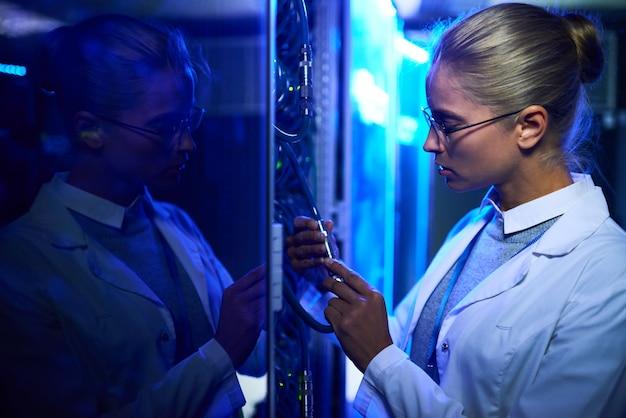 Femme scientifique travaillant avec des serveurs de superordinateurs