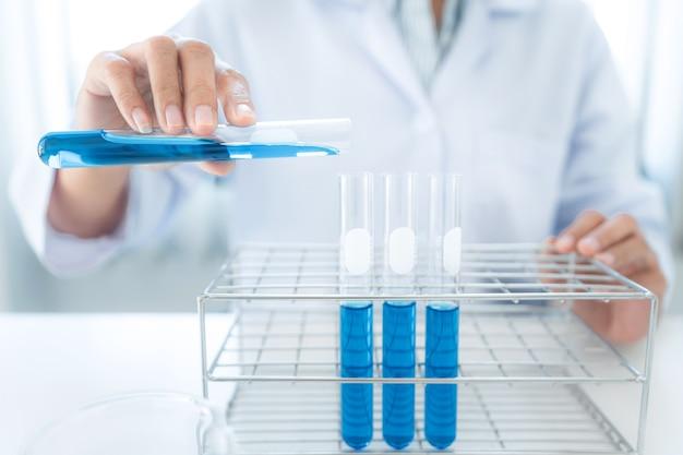 Femme scientifique versant un liquide bleu dans un tube à essai pour faire des expériences avec un microscope et une substance dans un tube à essai et un bécher tout en travaillant en laboratoire
