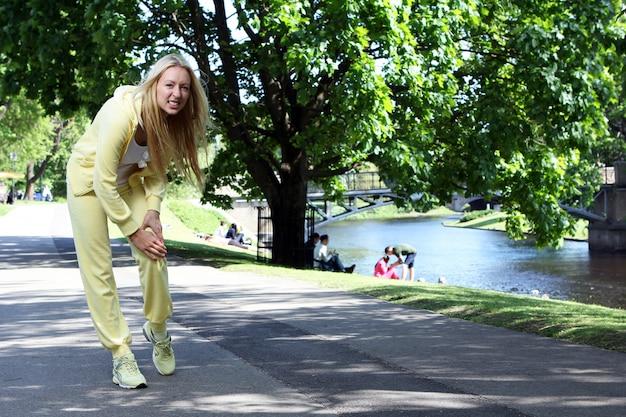 Une femme se blesse aux jambes tout en travaillant dans le parc