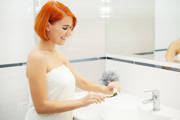 Femme se brosse les dents dans une salle de bain lumineuse