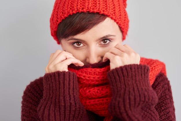 Femme se cachant dans des vêtements chauds