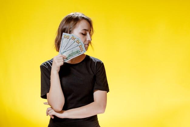 Femme se cachant derrière des tas de billets d'argent et célébrant sur fond jaune.