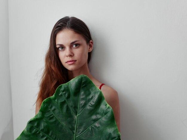 La femme se cache derrière un fond clair de feuille de fichier vert