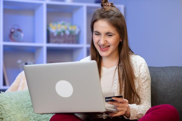 Femme se connectant avec un ordinateur portable et faisant des achats en ligne à l'aide d'une carte de crédit. jeune fille achète en ligne avec carte de crédit tout en étant assis sur le canapé. les femmes utilisent un ordinateur portable et effectuent des transactions en ligne