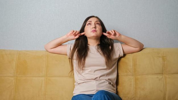 Une femme se couvre les oreilles et jure devant le bruit des voisins alors qu'elle est assise sur le canapé.