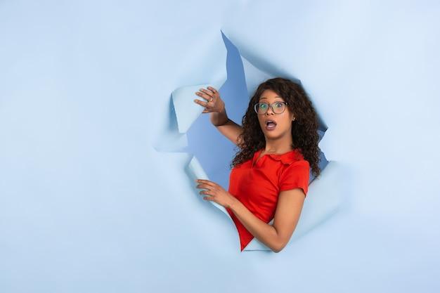 Femme se demandant saluant à travers le trou du mur de papier jaune