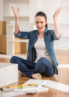Femme se déplaçant dans la nouvelle maison en essayant d'assembler la table.