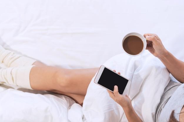 Une femme se détend sur le lit tout en utilisant un téléphone portable et une tasse de café dans les mains, une vue de dessus et un espace de copie.