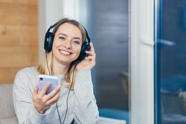 La femme se détend à la maison et écoute de la musique avec de gros écouteurs utilise un téléphone portable