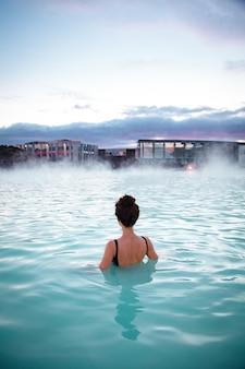 Une femme se détend et profite d'un spa dans le lagon bleu de source chaude dans la glace