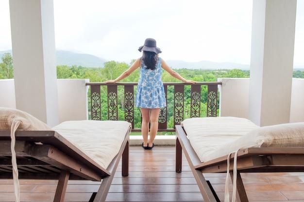 Femme se détendant à la vue de la montagne avec les bras ouverts en profitant de sa liberté