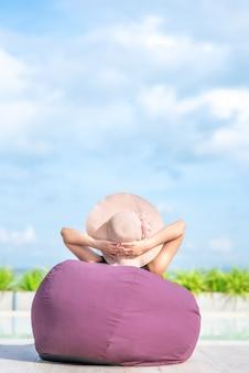 Femme se détendre au bord de la piscine en jour d'été