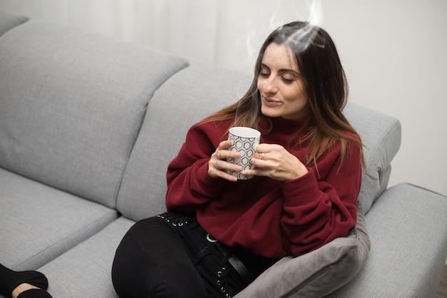 Femme se détendre en buvant une tasse de thé à la maison