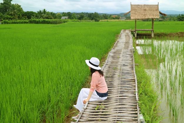 Femme se détendre sur le chemin de bambou au-dessus de la rizière verte, province de nan, nord de la thaïlande