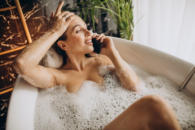 Femme se détendre dans le bain avec des bulles et parler au téléphone