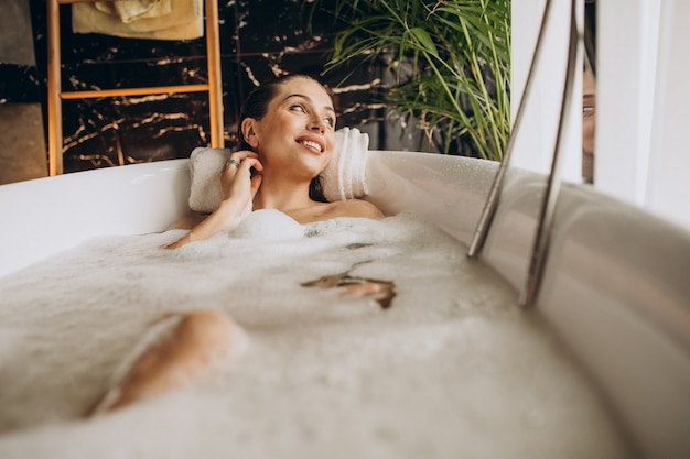 Femme se détendre dans le bain avec des bulles