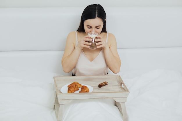 Femme se détendre dans le lit et boire une tasse de cappuccino chaud