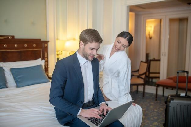 Une femme se détendre l'homme pendant qu'il travaille dans la chambre
