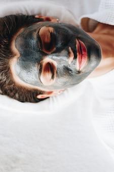 Femme se détendre avec un masque facial au charbon