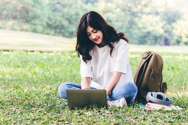 Femme se détendre avec un ordinateur portable assis sur l'herbe dans le parc