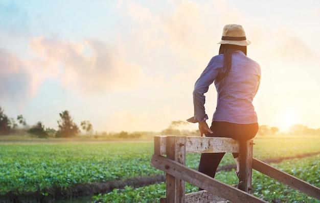 Femme se détendre et profiter de la vue du champ de chou frisé